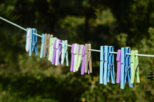 Colorful Plastic Clothespins On A Rope On A Green Plant Background