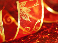Twisted Ornate Red Chiffon Gift Ribbon With Golden Glitter Ornament On Red Background