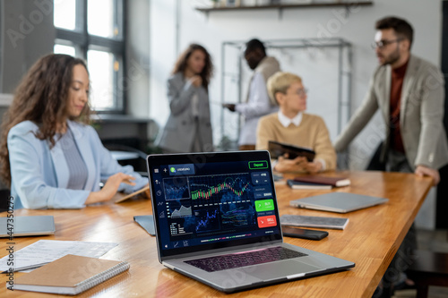 Fototapeta Laptop display with financial graph and other data on workplace where group of m