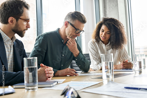 Focused doubtful mature businessman reading contract document thinking considering risks with professional lawyers legal experts executive team analyzing financial report sitting at office table.