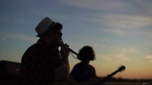 . Silhouette Of Young Talented Music Band Performing In City Embankment During Sunset. Stylish Bearded Singer And Guitarist Give Performance For Public In City Park.