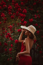 Elegant Beautiful Woman Wearing Luxury Wide Brim Straw Hat, Red Dress With Naked Back, Posing Near Blooming Roses