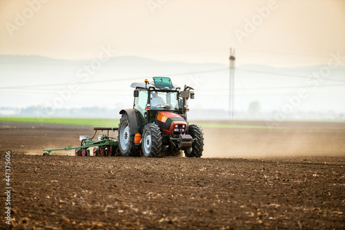 Fototapeta Farmer seeding, sowing crops at field