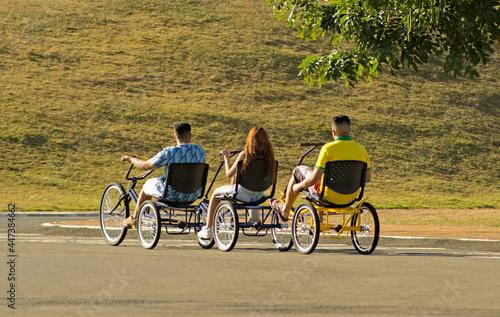 Fotografia, Obraz trio passeando em triciclo triplo no parque
