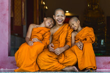 Buddhist Novice Monks Smiling And Sitting Together At Temple Gate