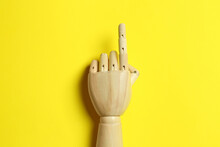Wooden Mannequin Hand On Yellow Background, Top View