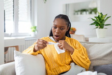 Ill African Young Woman Covered With Blanket Blowing Running Nose Got Fever Caught Cold Sneezing In Tissue Sit On Sofa, Sick Allergic Black Girl Having Allergy Symptoms Coughing At Home, Flu Concept