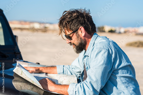 Fotografie, Obraz Man look a paper road trip map standing outside the car with blue sky and ground