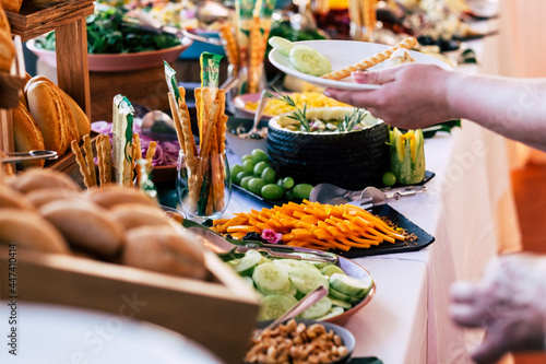 Fototapeta Close up of people taking food from table at event party with catering self serv
