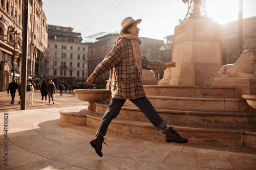 Fotomural Pretty cool woman jumps near statue in old European city square