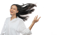 Smiling Asian Girl Wearing A Towel Is Standing With Her Long Black Hair Blowing By Wind On Gray Background