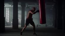 Man Hitting Punch Bag During Intense Workout. Male Boxer Practicing Kickboxing