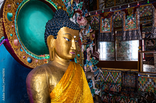 Murais de parede huge buddha golden statue decorated with religious flags and offerings at evenin