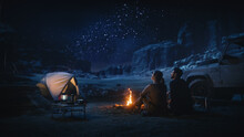 Happy Couple Tent Camping In The Canyon, Sitting By Campfire Watching Night Sky With Milky Way Full Of Bright Stars. Two Travelers In Love On A Romantic Vacation Trip. Back View Shot