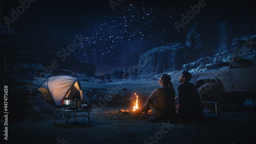 Cuadros en Lienzo Happy Couple Tent Camping in the Canyon, Sitting by Campfire Watching Night Sky with Milky Way Full of Bright Stars