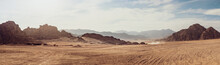 Safari And Travel To Africa, Extreme Adventures Or Science Expedition In A Stone Desert. Sahara Desert At Sunrise, Mountain Landscape With Dust On Skyline, Hills And Traces Of The Off-road Car.