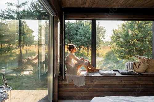 Photographie Young woman resting at beautiful country house or hotel, sitting on the window sill enjoying beautiful view on pine forest