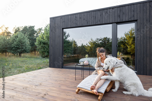 Murais de parede Woman resting on sunbed on wooden terrace near the modern house with panoramic windows near pine forest while playing with pet