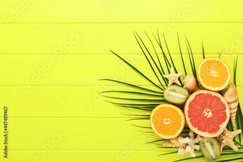 Canvas Print Fresh fruits with seashells and palm leaf on green wooden table