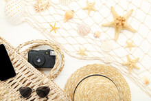 Starfishes With Seashell, Straw Hat, Sunglasses And Retro Camera On White Wooden Table