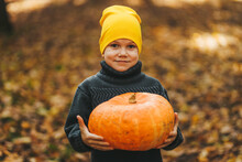 A Small Teenage Boy In A Yellow Hat And Warm Clothes Is Walking And Having Fun In An Autumn Park In Nature, A Child Is Holding A Pumpkin In His Hands, A Selective Focus
