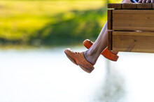 A Female Sits On The Edge Of A Footbridge And Swings Her Legs Over The Lake Water