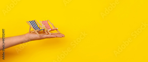 Fotografia sunbeds on hand, summer vacation, panoramic layout over yellow background