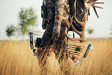 Close Up Shot Of A Hunter Dressed In Camouflage Clothing Holding A Modern Bow.