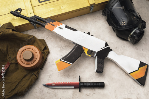 Obraz na plátne Wooden toy machine gun and bayonet knife on the table, top view
