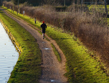 Lone Jogger On A Canal Towpath