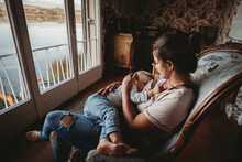 Mother Breastfeeding Baby On Chair In Vintage Room Looking Out On Lake
