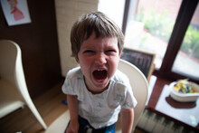 High Angle View Of A Boy Crying Sitting On A Chair At Home