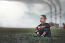 Little Boy Sitting On The Grass Environmental Pollution Concept.