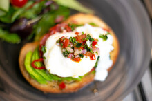 Mouthwatering Selective Focus Shot Of Eggs Benedict With Jalapeno Peppers And Sour Cream