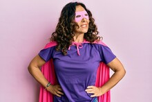 Middle Age Hispanic Woman Dressing As Superhero Wearing Pink And Purple Feminist Colors, Smiling With Confidence