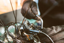 Hands Of A Bicycle Mechanic Wearing Gloves Using An Allen Key To Tighten Bolts While Working In A Workshop