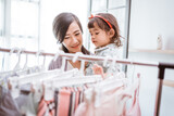beautiful asian mother taking her daughter to buy clothes
