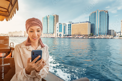 Fototapeta Happy asian woman in a maroon turban using app on her smartphone while cruising on a traditional Abra Dhow boat on Dubai Creek