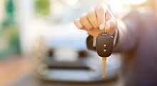 A Man Holding A Car Key In Front Of A Car At A Showroom