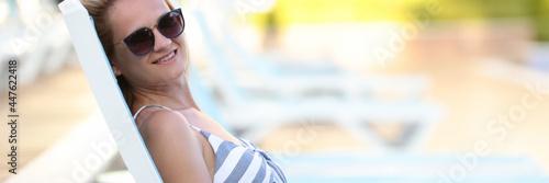 Fotografia Portrait of smiling woman in sunglasses lying on sunbed