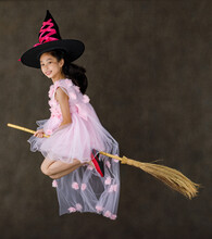 Portrait Studio Shot Of Little Cute Asian Kid In Pink Witch Dress Costume With Black High Hat Look At Camera Posing Flying Gesture Riding Magic Witchcraft Broomstick On Halloween Traditional Festival