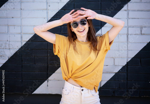 Portrait of a young happy girl woman in sunglasses and a yellow t-shirt on the street against a wall background, urban style