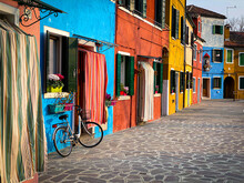 Bike Placed On The Facade Of A Multicolored House In Burano Island, Venice