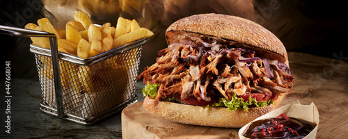 Pulled pork burger and French fries on table