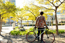 African American Man In City Holding His Bike