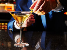 A Cocktail Being Garnished With Lemon Zest
