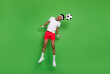 Full Length Photo Of Funny Impressed Dark Skin Man Wear White T-shirt Jumping High Beating Ball Isolated Green Color Background