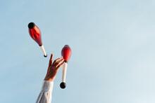 Juggler Performing Circus Trick Against Blue Sky