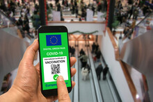 A Man In A Shopping Mall Holds A Smartphone With The European Union Digital Green Pass For Covid-19 In His Hand. Safety Concept For Coronavirus And The Green Pass