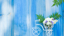 Flower Composition. Small Decorative Bicycle With A Bunch Of Flowers On A Blue Wooden Background. Image With Selective Focus
